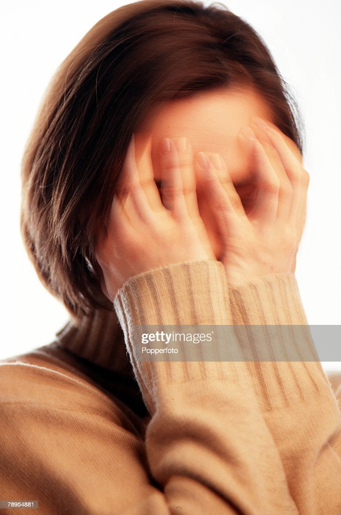 Blurred effect portrait of a young woman (age 20-22) holding her hands up over her eyes and forehead