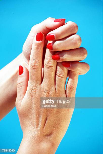 Stock Photography Close up of a womans well manicured hands with red nail polish one hand smoothing over the other