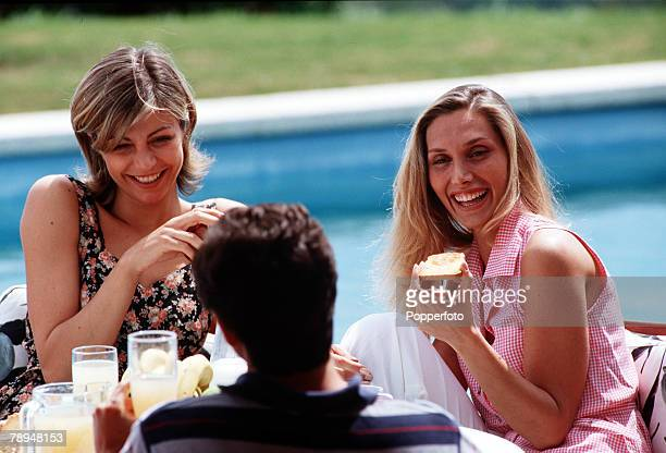 Stock Photography Group of young people enjoying a poolside breakfast of fresh fruit toast and juice The two women laugh as they chat to a man