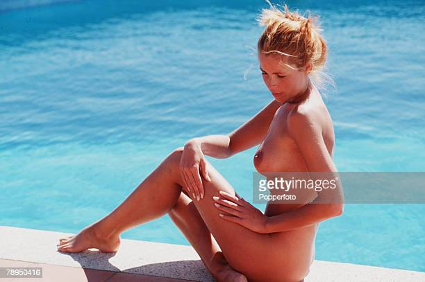 Naked tanned woman sitting at the edge of a swimming pool smoothing her hands over her thighs