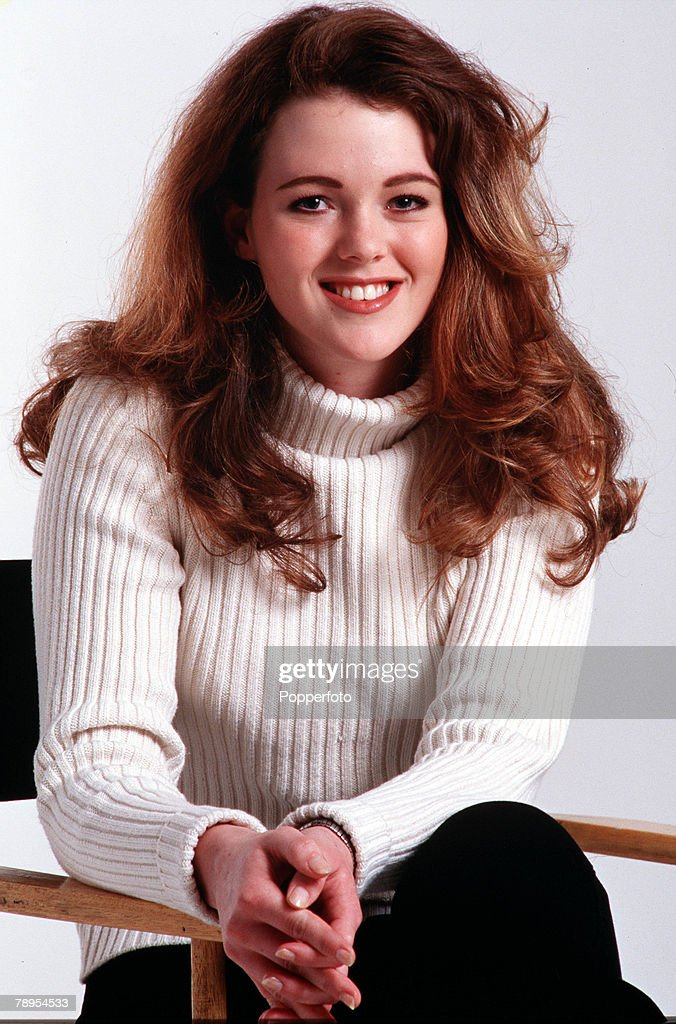 Stock Photography: Portrait of a smiling young girl (age 18-20) sitting on a chair, wearing a white ribbed sweater and black trousers; long auburn hair and blue eyes. : News Photo