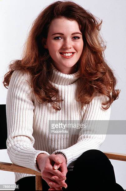 Portrait of a smiling young girl sitting on a chair wearing a white ribbed sweater and black trousers long auburn hair and blue eyes