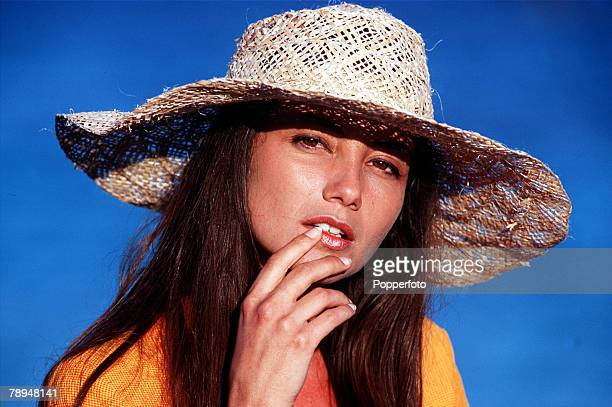 Stock Photography Portrait of a young woman wearing a large straw sunhat and orange linen jacket looks pensively at the camera with her finger on her...