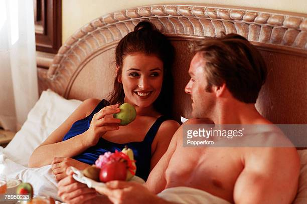 Smiling couple enjoying a healthy breakfast of fresh fruit in bed The woman is offering the man an apple