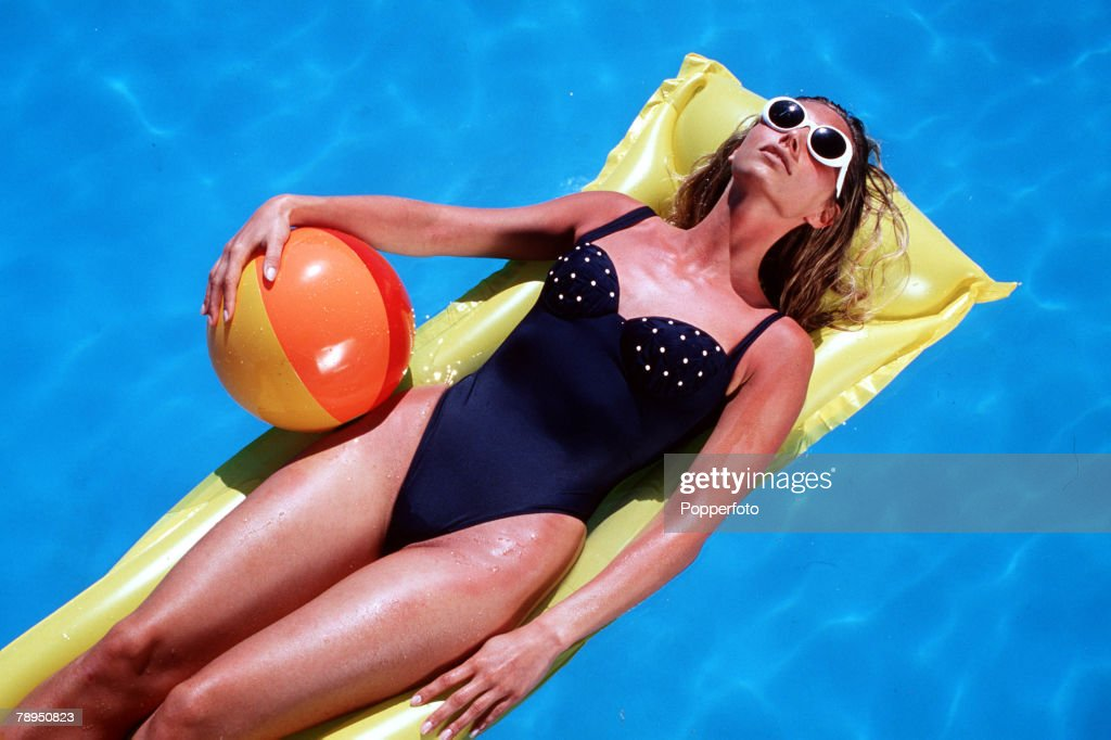 Stock Photography: Tanned woman wearing swimming costume and sunglasses, floating on a lilo in a pool, and clutching a beach ball. Overhead view looking down. : News Photo