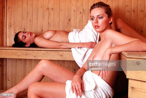 Stock Photography Two nude women inside a sauna relaxing in the heat one lying on a bench with a towel over her waist and the other seated with towel...