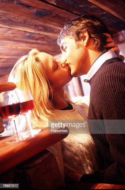 Young couple embrace and kiss passionately after a glass of red wine in a warm rustic room