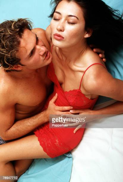 Stock Photography Young couple engaged in a sensual embrace in bed The woman who is wearing a sexy red nightdress has her eyes closed as the man who...
