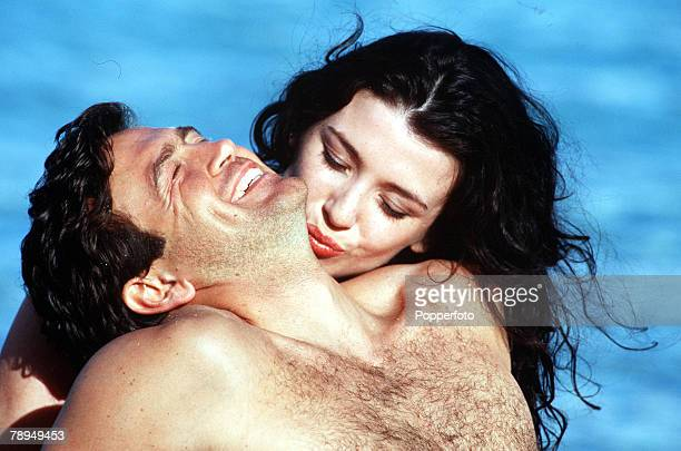 Young couple enjoying a passionate moment by the sea in the warm sun