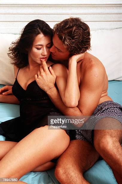 Stock Photography Young couple sitting close together in bed touching and caressing each other