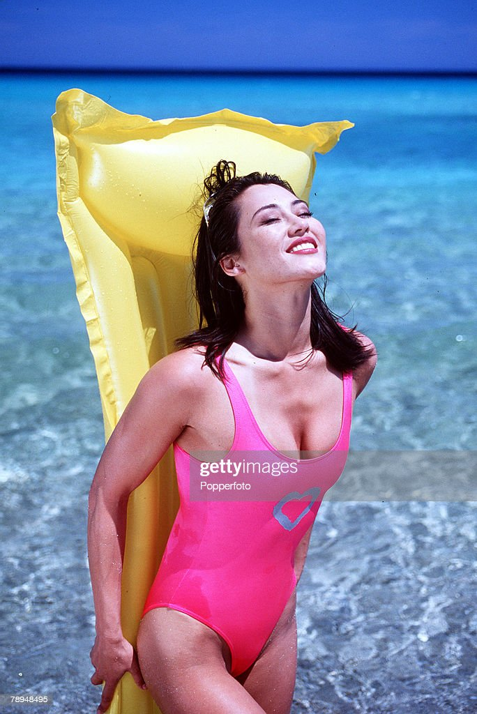 Stock Photography. Young glamourous woman wearing bright pink swimming costume, stands at the water+s edge with a yellow lilo held tight against her back as she enjoys the warm sunshine. : Nachrichtenfoto