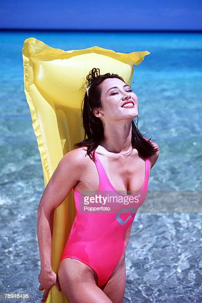 Stock Photography Young glamourous woman wearing bright pink swimming costume stands at the waters edge with a yellow lilo held tight against her...