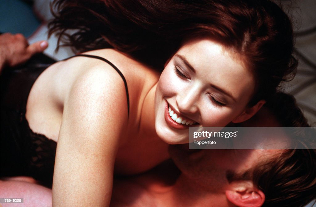 Stock Photography. Young partly dressed couple enjoying a passionate embrace in bed. : News Photo
