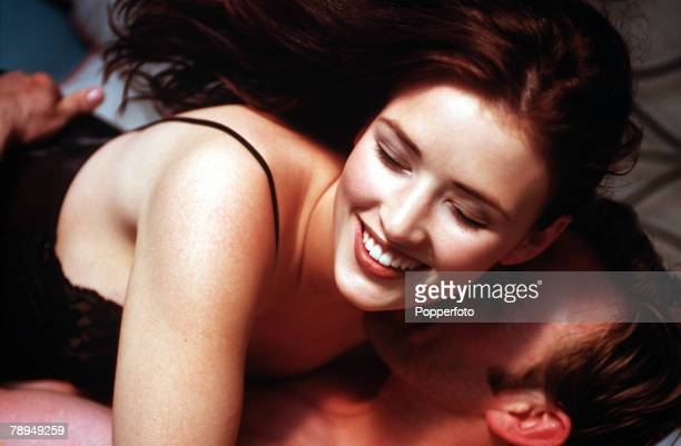 Stock Photography Young partly dressed couple enjoying a passionate embrace in bed