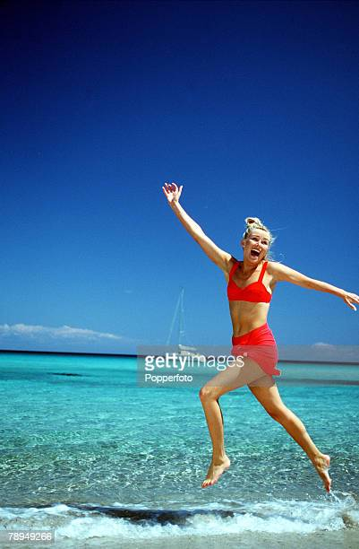 Stock Photography Young woman wearing red bikini and wrap leaping along the waters edge on a tropical beach with her arms outstretched A yacht can be...