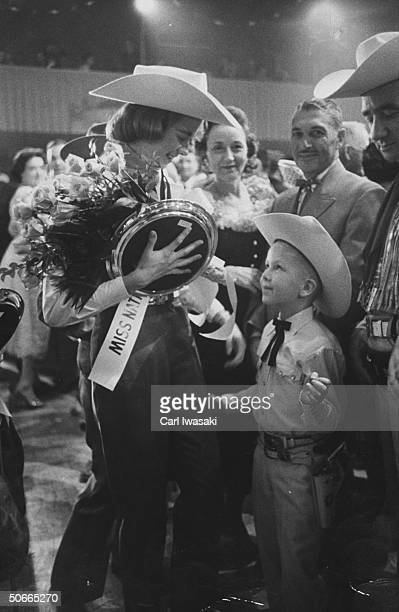 Stock show queen Judy Johnston receiving roses from small boy for winning