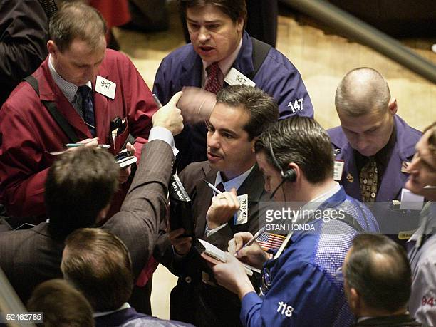 A stock specialist shouts prices to traders crowding around a company's post on the floor of the New York Stock Exchange just after the opening bell...
