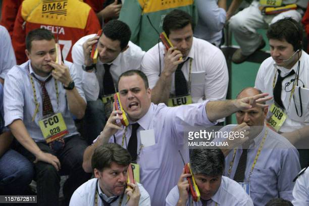 A stock trader gestures while negotiating in the iBovespa future index pit during the morning session at the Mercantile and Futures Exchange in Sao...