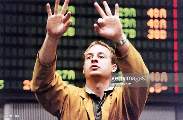 Stock trader gesturing in front of trading board, close-up