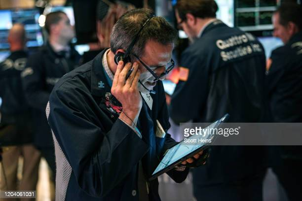 Stock trader Gregory Rowe works on the floor of the New York Stock Exchange on February 28 2020 in New York City Markets continued their downward...