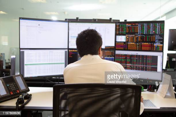 stock trader looking at screens - börsensaal stock-fotos und bilder