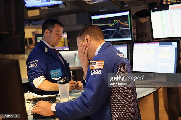 A stock trader makes last minute transactions ahead of the closing bell at the New York Stock Exchange on August 27 2013 in New York City The Dow...