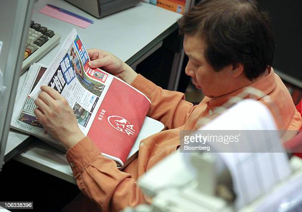 A stock trader reads a newspaper showing an AIA Group Ltd advertisement during the trading debut of AIA Group at the stock exchange in Hong Kong...