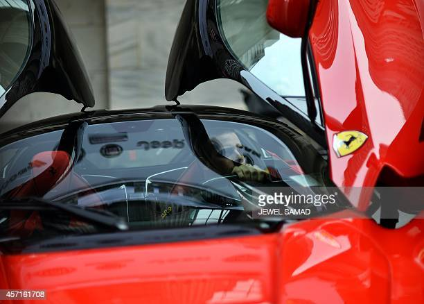 A stock trader tries the driving seat of a Ferrari LaFerrari dsplayed in front of the New York Stock Exchange on October 2014 in New York Italian...