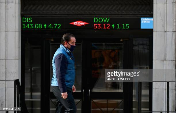 Stock trader walks past the New York Stock Exchange at Wall Street on November 16, 2020 in New York City. - Wall Street stocks rose early following...