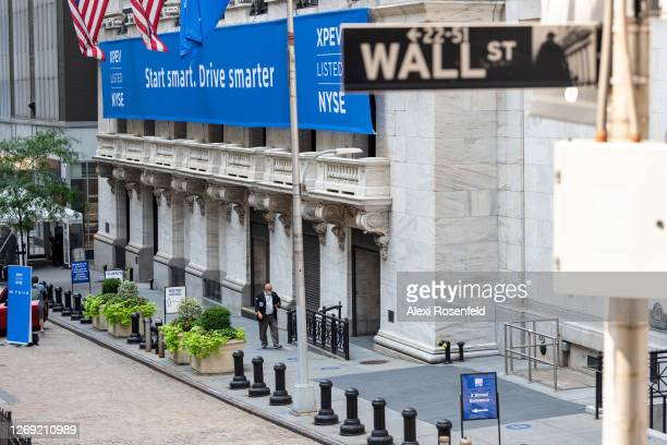 Stock trader wearing a mask walks near social distancing signs the day a new IPO is launched at the New York Stock Exchange as the city continues...