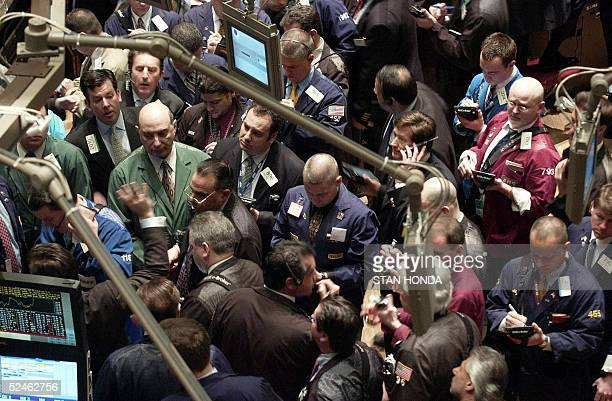 Stock traders crowd around a company's post on the floor of the New York Stock Exchange just after the opening bell 21 March 2005 Wall Street shares...
