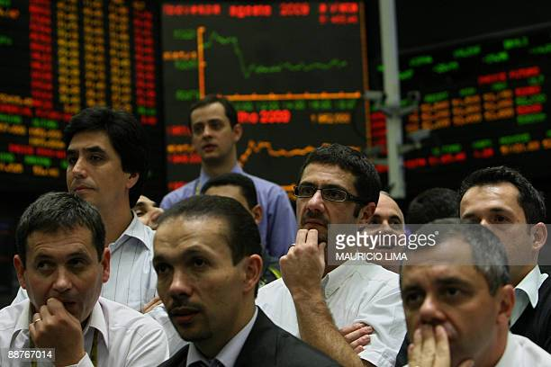 Stock traders listen to the final speech after the closing trading session negotiated by traders at the main floor of the Mercantile and Futures...