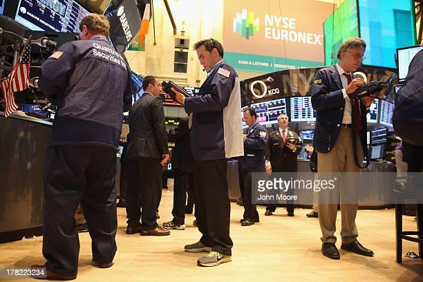 Stock traders make last minute transactions ahead of the closing bell at the New York Stock Exchange on August 27 2013 in New York City The Dow Jones...