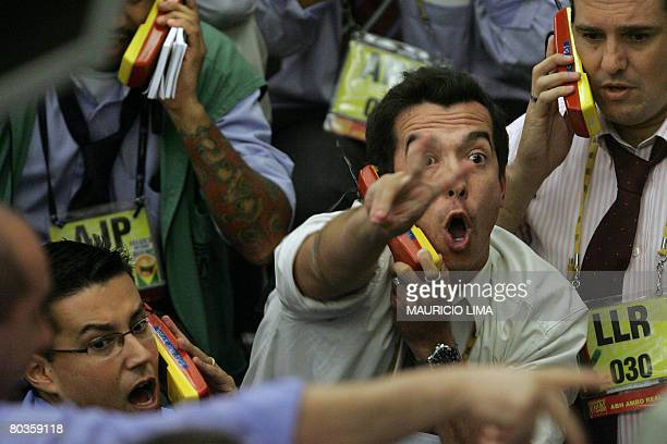 Stock traders negotiate in the spot dollar pit prior to the closing time at the Mercantile Futures Exchange in Sao Paulo Brazil on March 24 2008...