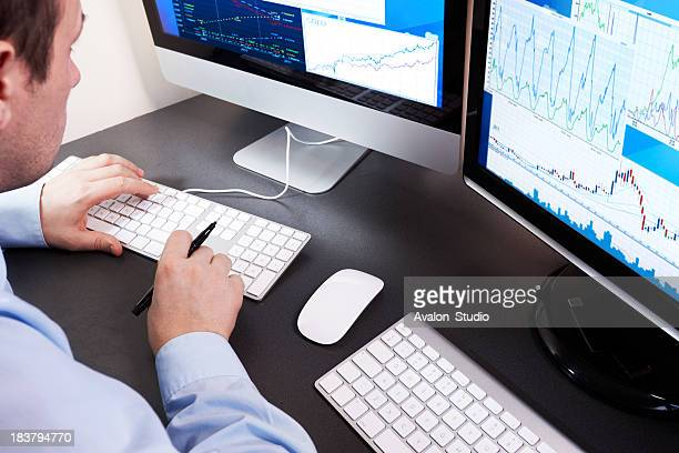 Stockbroker checks the financial results on the computer.
