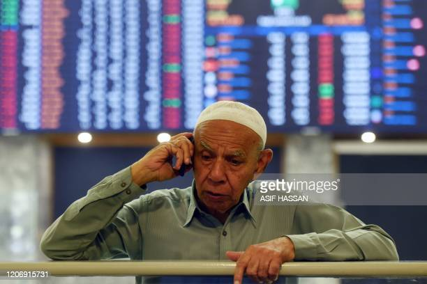 A stockbroker monitors share prices at the Pakistan Stock Exchange in Karachi on March 13 2020