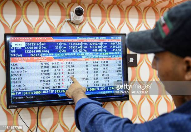 A stockbroker points out the latest share prices on a screen during a trading session at the Pakistan Stock Exchange in Karachi on August 26 2019