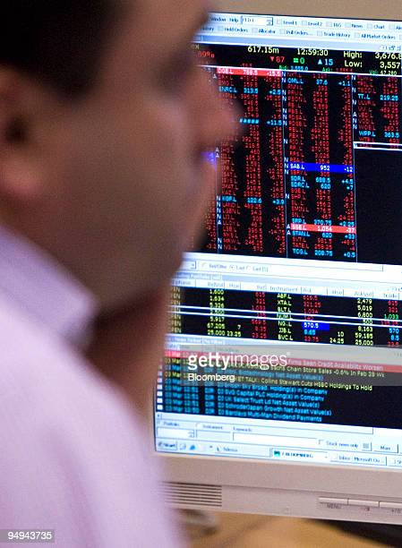 A stockbroker studies share prices on his computer screens at Shore Capital Markets in London UK on Tuesday March 3 2009 UK stocks retreated for a...