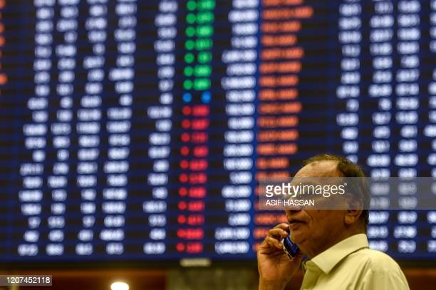 A stockbroker talks on his cellphone as he watches the latest share prices during a trading session at the Pakistan Stock Exchange in Karachi on...