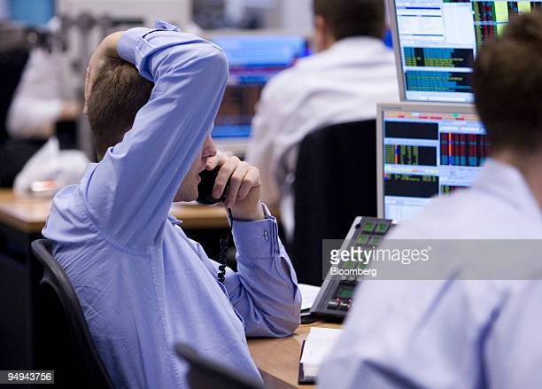A stockbroker talks on the telephone while working at his desk at Shore Capital Markets in London UK on Tuesday March 3 2009 UK stocks retreated for...