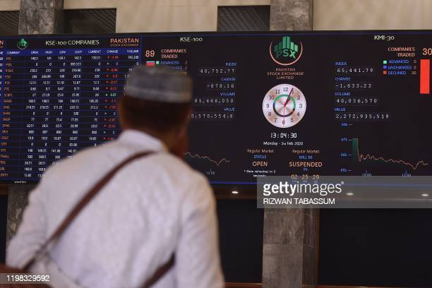 A stockbroker watches an index board showing latest share prices during a trading session at the Pakistan Stock Exchange in Karachi on February 3 2020