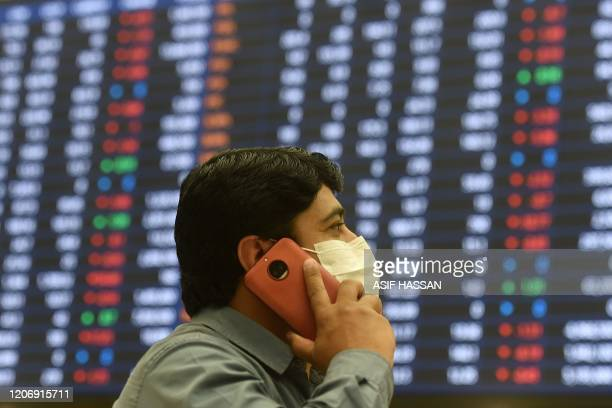 A stockbroker wearing a facemask amid concerns of the spread of the COVID19 coronavirus speaks on his cellphone as he watches share prices on a...