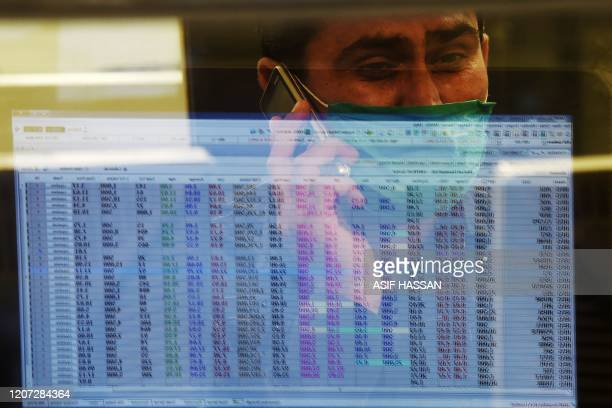 A stockbroker wearing a facemask amid concerns over the spread of the COVID19 novel coronavirus watches the share prices during a trading session at...