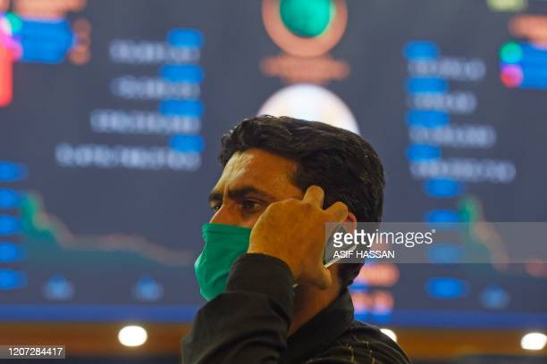 A stockbroker wearing a facemask amid concerns over the spread of the COVID19 novel coronavirus holds a mobile phone during a trading session at the...