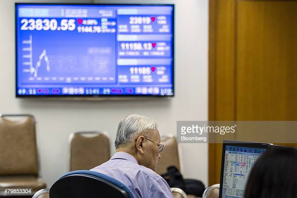 A stockbroker works in front of a screen displaying share prices at a securities brokerage in Hong Kong China on Wednesday July 8 2015 Investors...