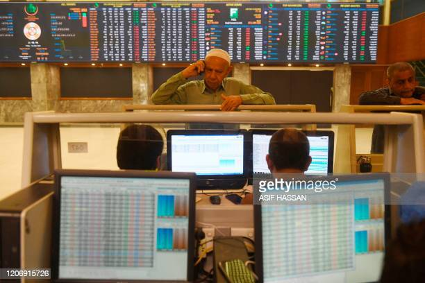 Stockbrokers monitor share prices at the Pakistan Stock Exchange in Karachi on March 13 2020