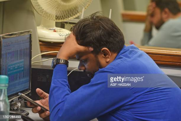 Stockbrokers react as they watch the latest share prices during a trading session at the Pakistan Stock Exchange in Karachi on March 16 2020