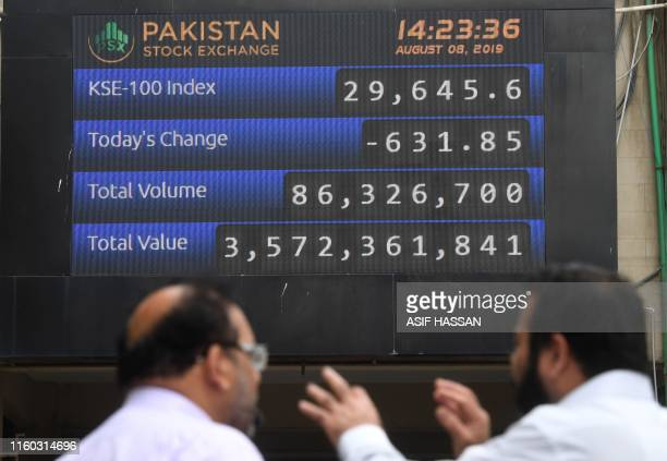 Stockbrokers watch an index board displaying latest share prices outside the Pakistan Stock Exchange in Karachi on August 8 2019