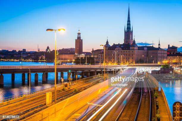Stockholm commuter train zooming through Gamla Stan illuminated dusk Sweden