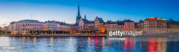 stockholm lamplight illuminating gamla stan kornhamnstorg waterfront sunset panorama sweden - scandinavian ethnicity stock pictures, royalty-free photos & images